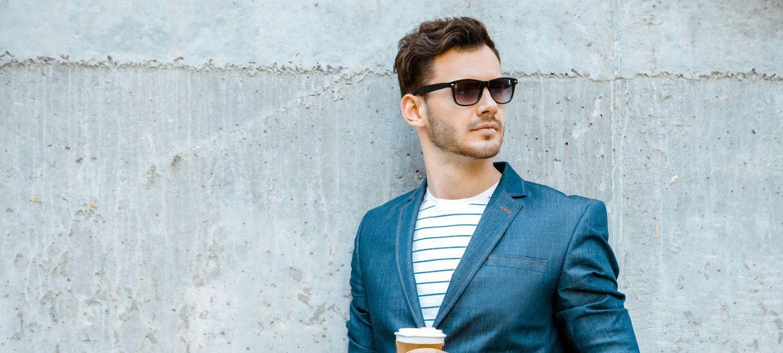 Uomo vestito casual appoggiato a una parete con in mano un caffé da portar via