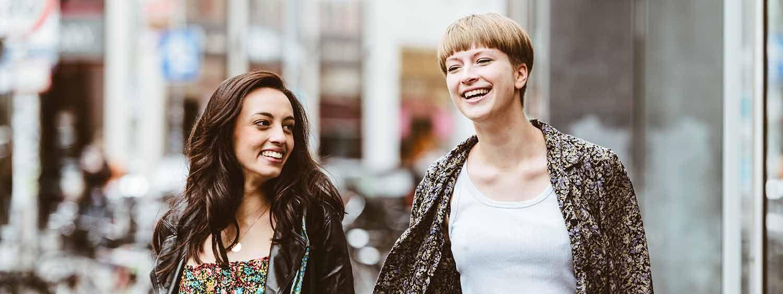 Braunhaarige Frau mit langer, welliger Mähne lachend neben blonder, kurzhaariger Frau