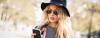 Junge Frau mit langen blonden Locken, Hut und Sonnenbrille