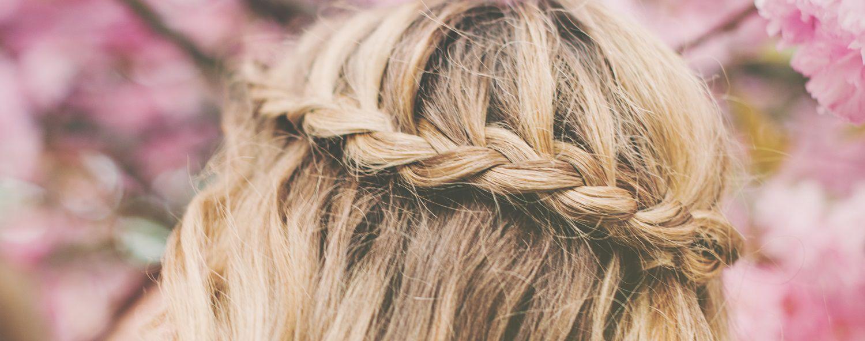 Primo piano della capigliatura di una donna con capelli biondi e semicorona intrecciata