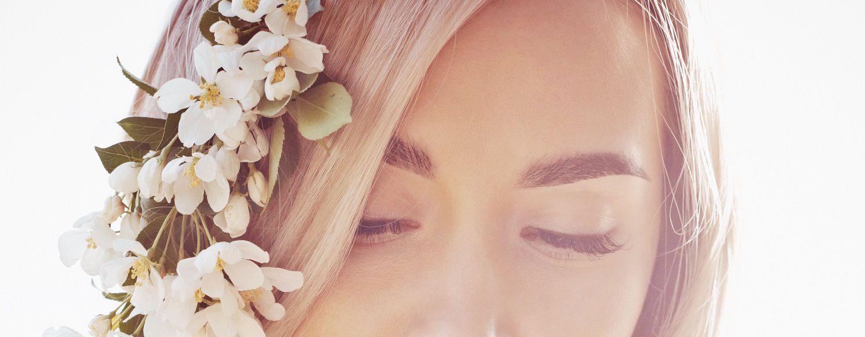 Donna con capelli biondi lunghi intrecciati con fiori.