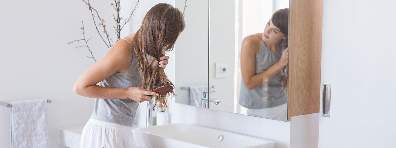 Kobieta rozczesująca włosy przed lustrem