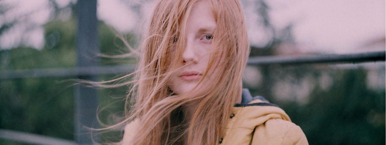 Jeune femme au visage balayé par de longs cheveux blond miel