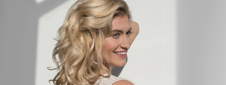 Blondinka se dotika las in se nasmehne