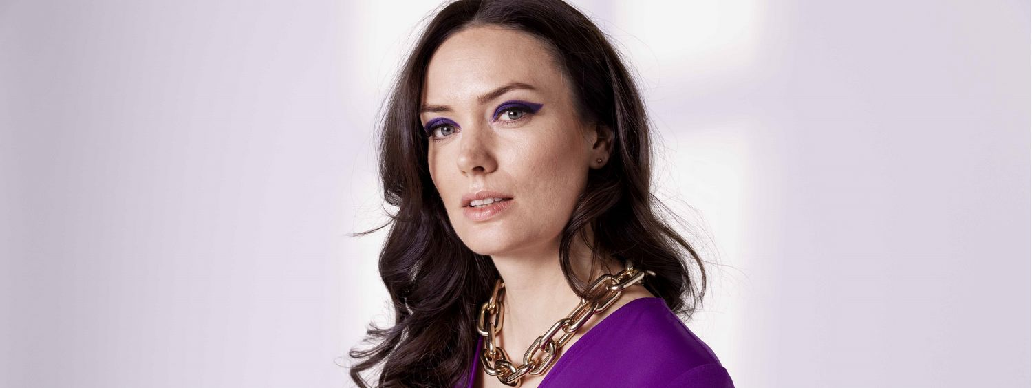 Woman with brunette hair, purple dress and chunky necklace
