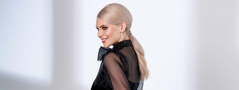 Ženska s platinasto blond lasmi v elegantnem nizkem čopu.