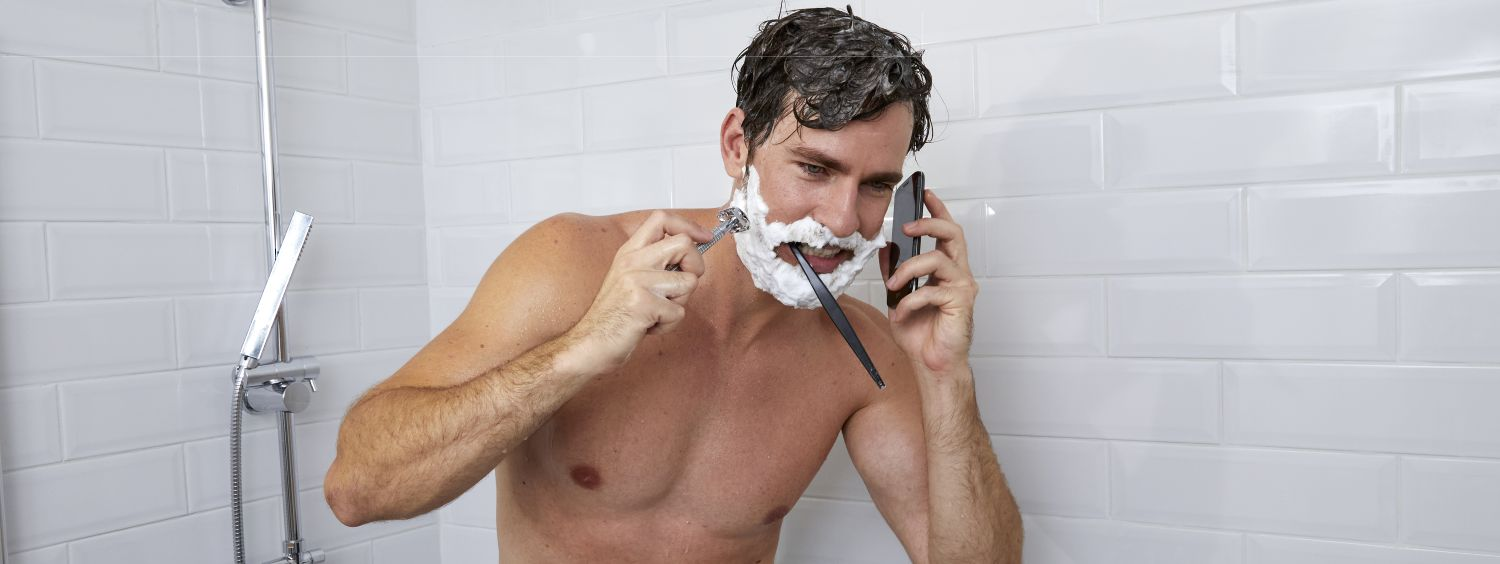 Man on the phone, shaving, and brushing his teeth while in the shower.