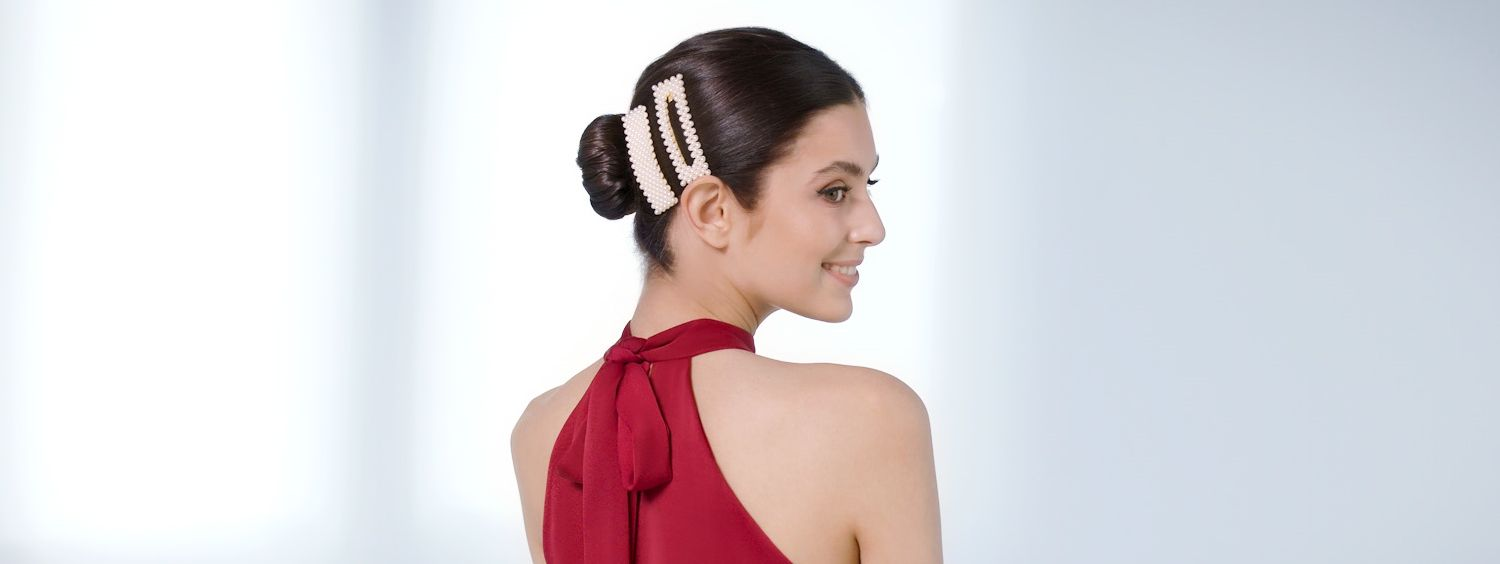 Woman with bun hairstyle, accessorizing it with slides.