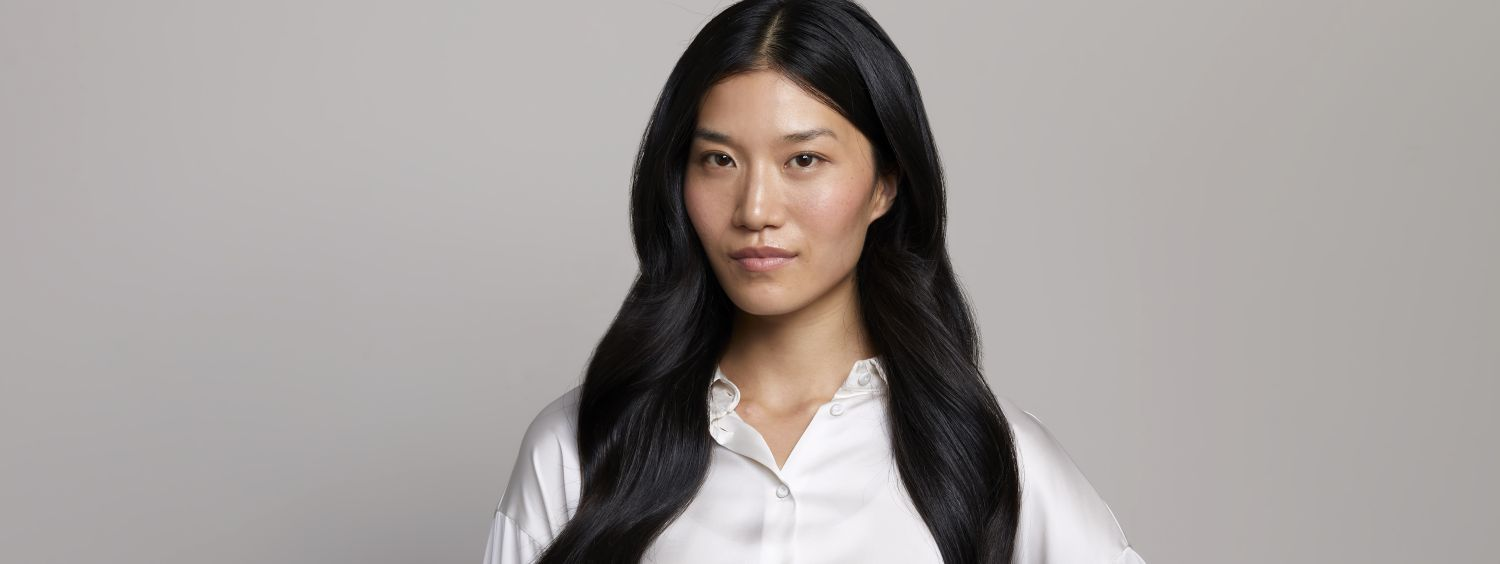 Woman with long black, healthy hair wearing a white blouse.