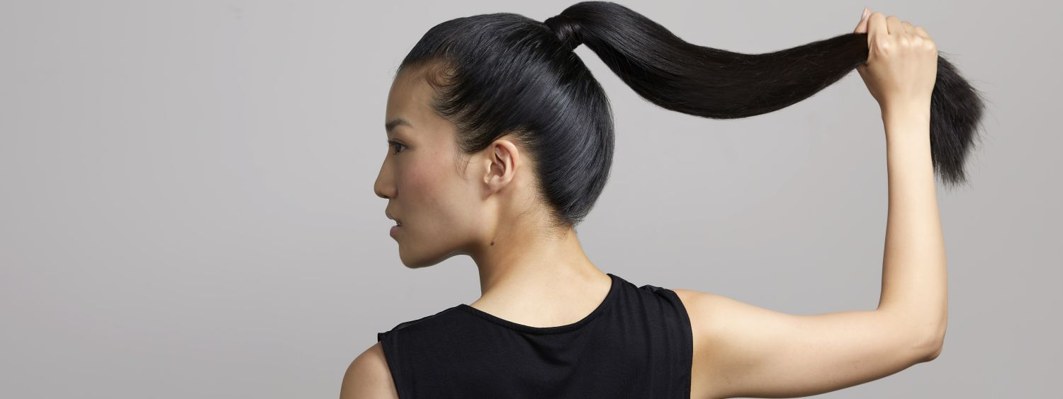 Woman with long glossy black hair, holding her ponytail.
