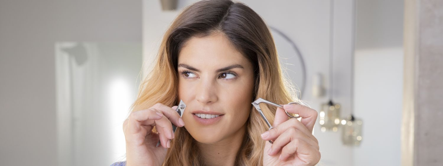 Woman looking devious as she holds a broken pair of scissors