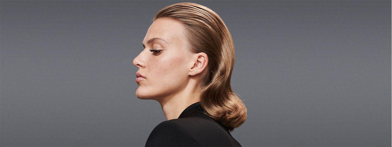 Seitenansicht einer brünetten Frau mit zurückgekämmter 40er-Jahre-Frisur und schwarzem Oberteil