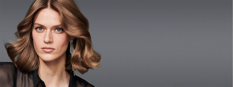 Frontansicht einer brünetten Frau mit welligem, halblangem Haar