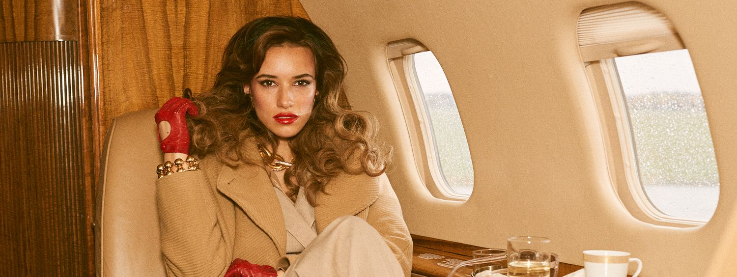 Confident, well-styled businesswoman sits in a private jet, twirling her hair