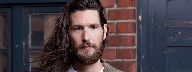 Mannequin aux longs cheveux bruns avec une barbe