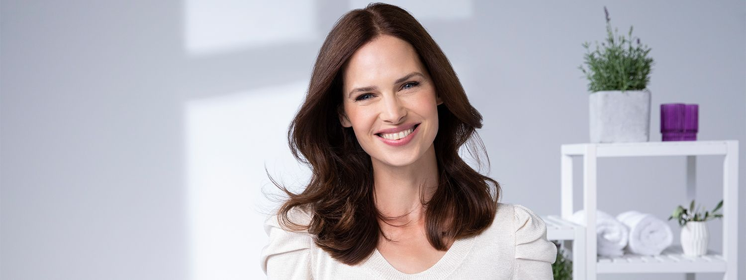 Woman with newly-dyed healthy-looking brunette hair smiles at camera