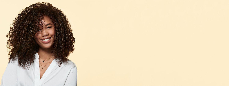 Mlada žena kovrdžave kose u beloj bluzi