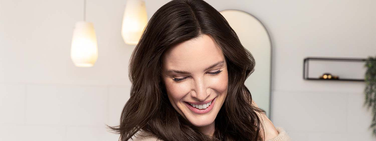 Woman with dark brown hair smiles while looking down and touching her hair