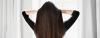Frau mit langem dunkelbraunen Haar steht mit dem Rücken zur Kamera, fasst sich in die Haare und schaut aus dem Fenster