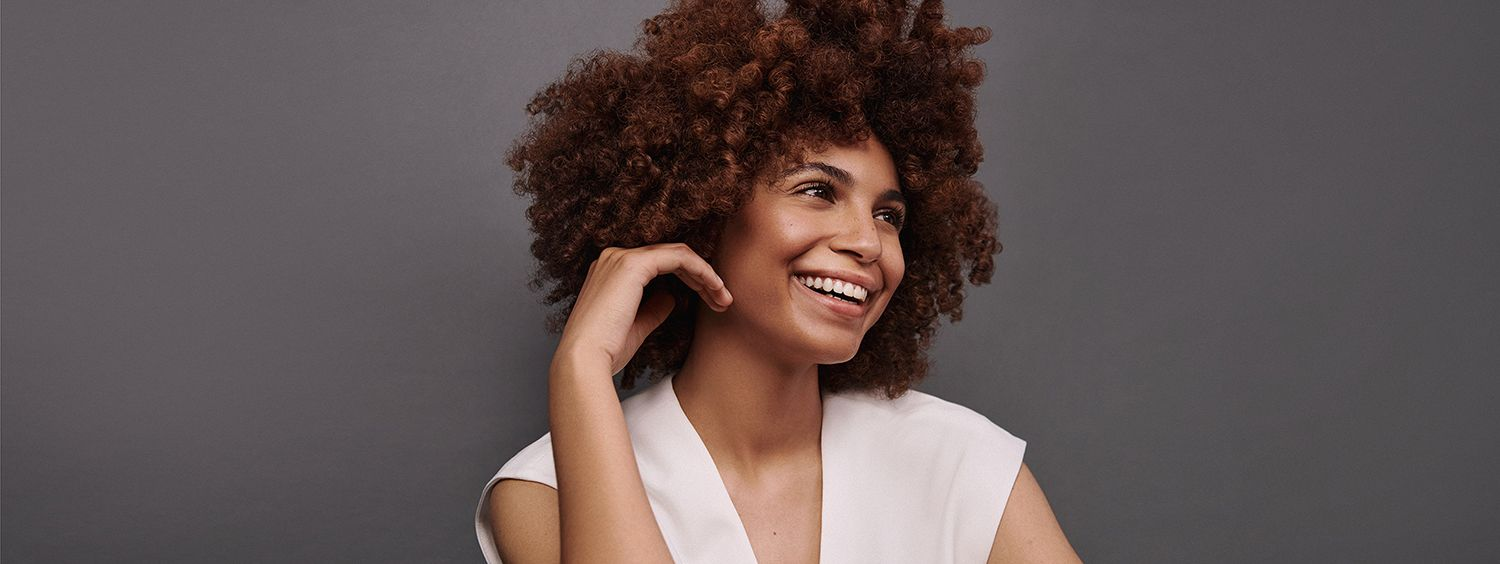 Woman with brunette curly afro smiles and touches her hair