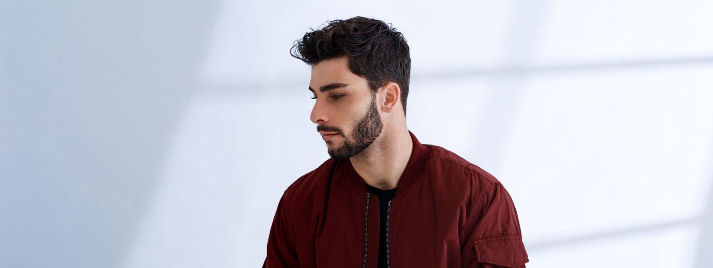 Dunkelhaariger Mann mit Bart trägt eine dunkelrote Jacke