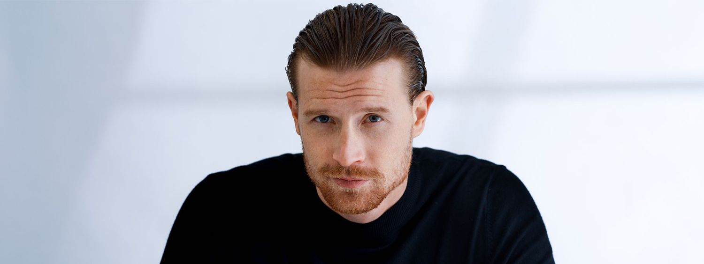 Rothaariger, bärtiger Mann in schwarzem Pullover mit längeren Haaren, die zum Sleek Look gestylt sind