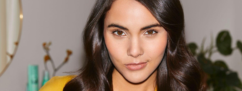 Woman with dark, shiny, wavy hair looks confidently into the camera
