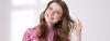Braunhaarige Frau mit pinkfarbener Bluse fasst sich ins Haar