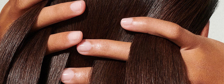 Woman runs her fingers through her sleek brunette hair