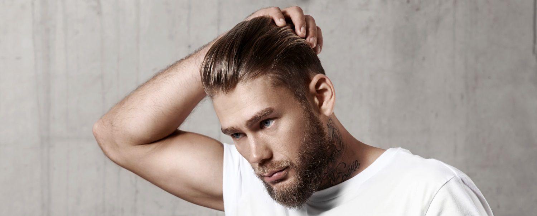 Homme blond en train de plaquer ses cheveux vers l'arrière avec de la cire.