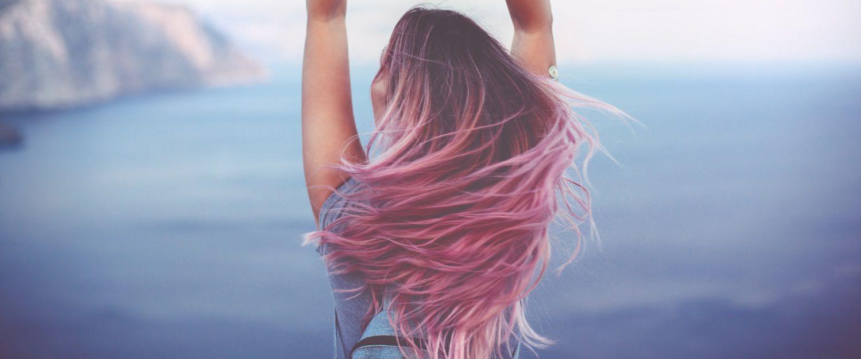 Donna di spalle con capelli castano rosa al vento che guarda dall'alto il mare