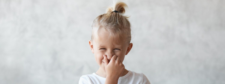 Bambino che ride portandosi la mano alla bocca, con capelli raccolti in una piccola coda a fontana