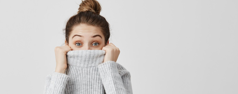 Primo piano di donna con occhi azzurri, maglione a collo alto e faccia stupita