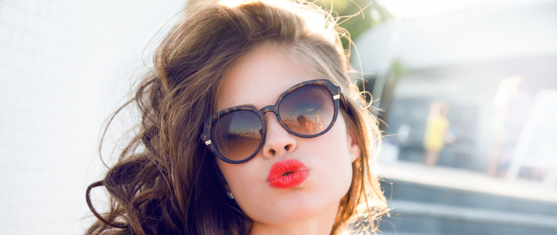 Donna con boccoli, occhiali da sole e rossetto rosso che manda un bacio