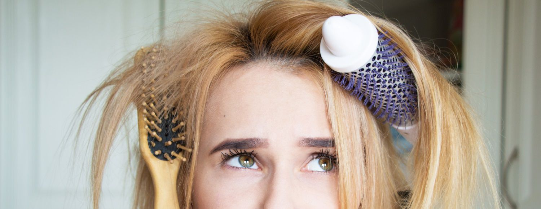 Donna con spazzole e pettini tra i capelli con espressione confusa