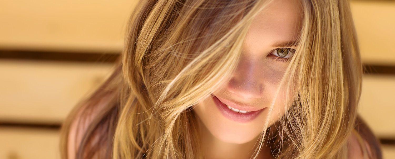 Donna con capelli lunghi scalati e sfumature tiger eye