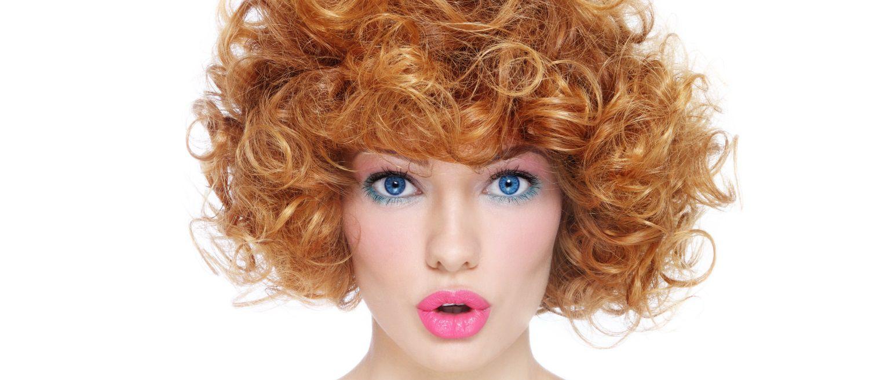 Donna con capelli rossi sopra le spalle ricci e voluminosi