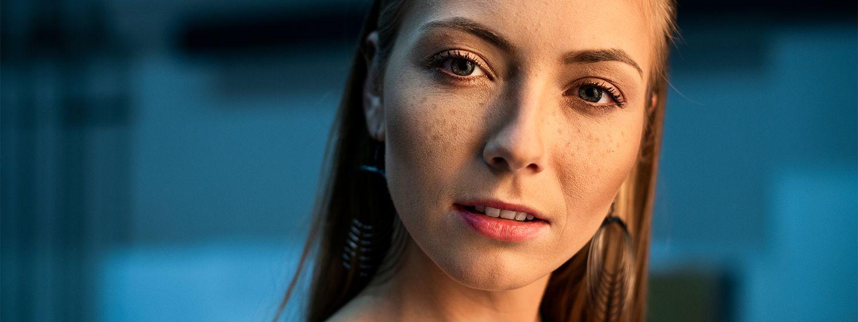 Femme blonde avec un wet look effet plaqué, des boucles d'oreilles et un haut transparent