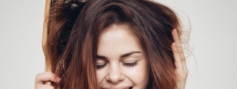 Ragazza dai capelli rossi in accappatoio che si afferra i capelli