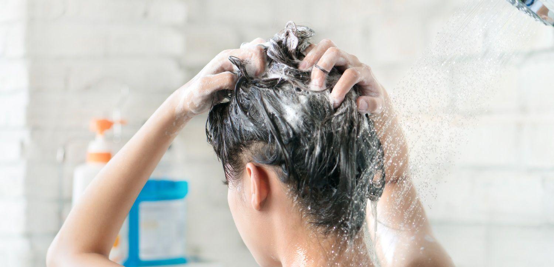 Donna che si fa lo shampoo sotto la doccia
