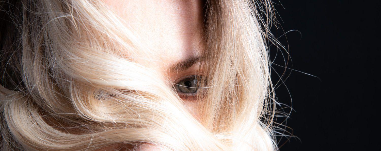 Donna con capelli biondo platino che porta le ciocche davanti al viso