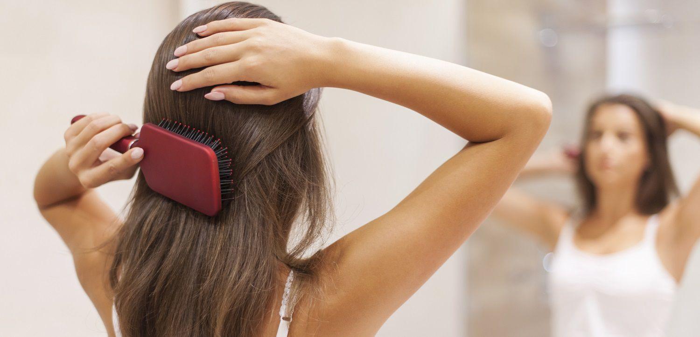 Donna che si spazzola i capelli allo specchio