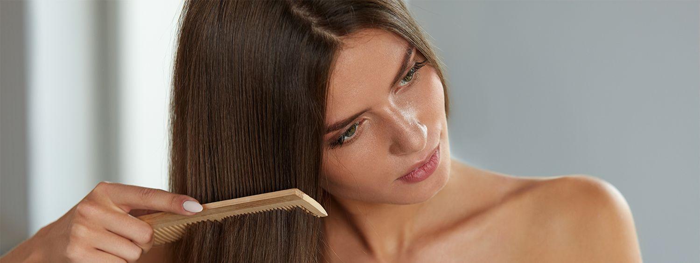Braunhaarige Frau mit glatten Haaren kämmt ihr Haar