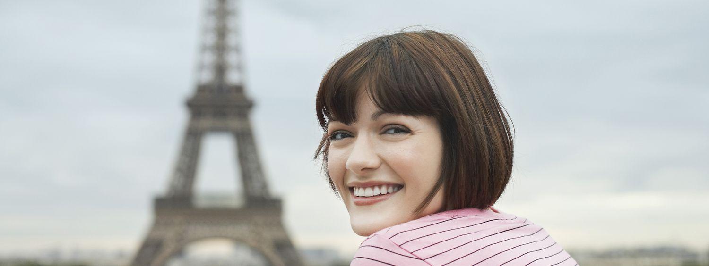 Frau mit braunem Pagenschnitt trägt ein rotes Ringelshirt, im Hintergrund sieht man den Eiffelturm