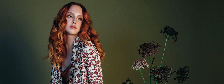 Jeune femme aux longs cheveux roux posant à côté de fleurs