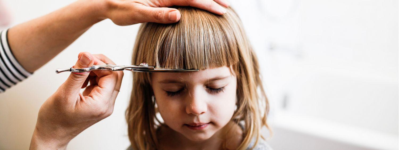 Maman en train de couper la frange de sa petite fille blonde