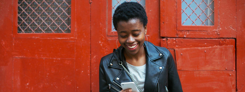 Schwarzhaarige Frau mit kurzen Haaren trägt Lederjacke und schaut auf ihr Handy