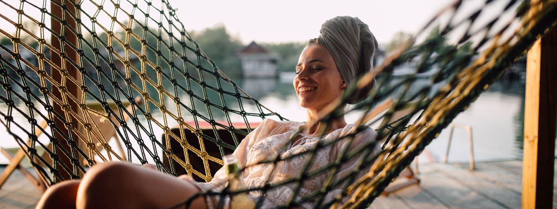 Frau mit Handtuchturban sitzt lächelnd in einer Hängematte