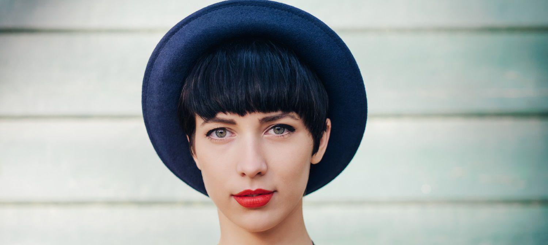 Donna con cappello elegante e capelli nero blu