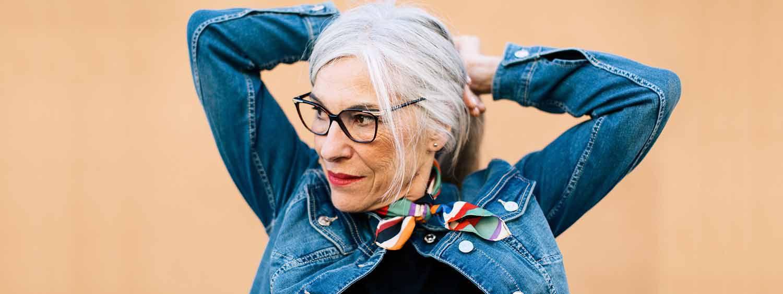Donna con capelli grigi naturali e occhiali che si fa una coda di cavallo